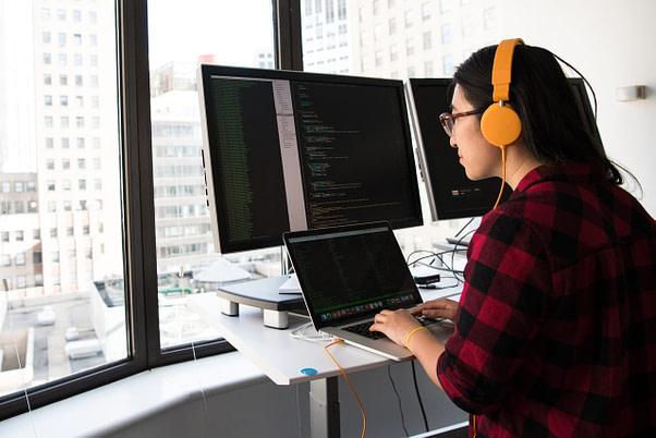 Mujer Programadora Trabajando Desde Su Oficina En Edificio Con Vista A La Ciudad. El Inglés Es Un Factor Fundamental Para Mejorar Las Oportunidades Laborales De Este Tipo De Profesionales Altamente Requeridos En Todo El Mundo.