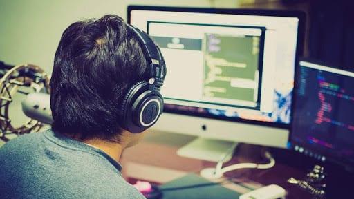 fotografía de ingeniero informático trabajado con múltiples computadores al mismo tiempo.