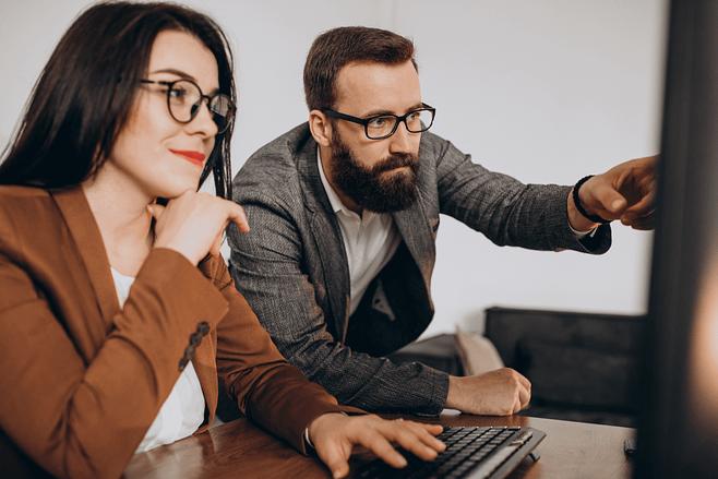 Hombre y mujer participan de una capacitación en inglés para empleados.